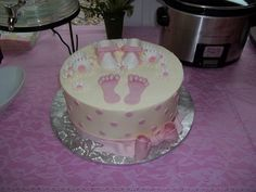 Baby shower cake for girl with booties and foot prints.