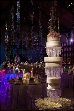 high end luxury chandelier cake fresh flowers expensive wedding details hanging from the high ceilings in Napa. Lighting By: The Lux Productions