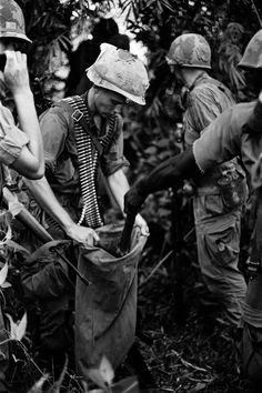 Military photographer Charlie Haughey. Soldiers load into bags weapons from a captured cache near Dau Tieng.