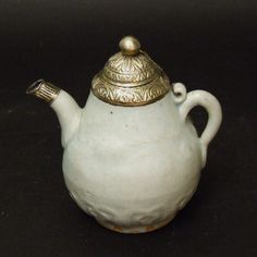 A Small Qingbai Porcelain Ewer, Yuan Dynasty Late 13th or 14th Century. The Baluster Form Moulded in Ill-defined Lower Relief with a Dragon Above Lappet Panels. The White Metal Mount and Cover are Probably 19th or Early 20thth Century Low Grade Silver from Indonesia.   References : For a related Yuan Qingbai ewer see : Chinese and South East Asian White Ware found in the Philippines (Oriental Ceramic Society of the Philippines, Oxford University Press, 1993. ISBN 0-19-588615-1) page 75 plate…