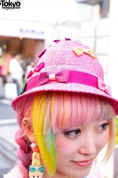 Kumamiki is wearing a bow-decorated dress from her own brand Party Baby with striped stockings and pink Tokyo Bopper platforms. Accessories include a pink hat (also covered in cute bows), a Party Baby shrimp earring, candy necklace, hair ties in her rainbow-colored hair, a bubble-blowing duckie necklace, pancake and strawberry rings, colorful 6%DOKIDOKI bracelets, and a cute straw handbag (with more shrimp) from Party Baby.