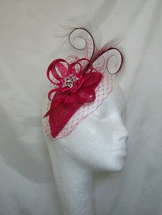Cerise Raspberry Pink Blusher Veil Curl Feather Teardrop Sinamay Fascinator £37.00 Order Now from www.indigodaisyweddings.co.uk Specialising in stunning bespoke cocktail fascinators and formal hats in a wide range of colours, perfect for Royal Ascot and The Kentucky Derby. Plus all your wedding floral accessories including shoe clips, vintage flapper bands, feather and flower fascinators, feather fans, fairy wands, wrist corsages, wedding bouquets & buttonholes. Worldwide Delivery.