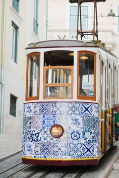 Tram in Alfama district, Lisbon   Portugal. The streets are so narrow that the tram brushes against the window boxes on both sides