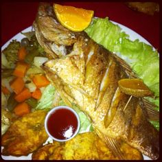 Pardo con patacones y vegetales. Fried red snapper along fried plantains and vegetables.