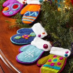 Felt Mitten Ornaments: Use pattern to cut the top mitten layer from wool felt. Continue adding and layering pieces until design is complete. To finish the ornament, sew one or two felted balls to the right corner of the cuff. Add a hanging loop.