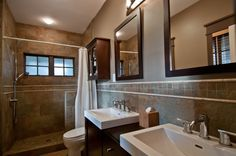 This smaller bathroom mixes natural stone tiles with dark wood. Frosted glass windows in the shower enclosure keep privacy without sacrificing light.