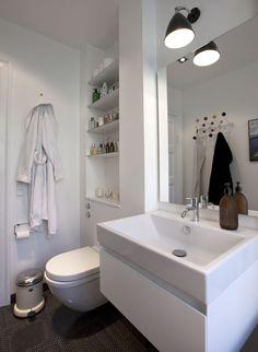 Parrets forkærlighed for sort-hvid indretning kommer til udtryk på badeværelset, hvor en væglampe fra Bestlite giver de hvide fliser fra Made a Mano kontrast. Indhakket over toilettet er udnyttet til hylder, og det giver masser af afsætningsplads til skønhedsgrej. I spejlet fra Bad & Stil ses en Eames-knagerække fra Paustian. Toilettet, Starck 3, er fra Duravit, mens pedalspanden er fra Vipp.