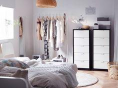 Makuuhuone, jossa kaksi viiden laatikon lipastoa ja valkoinen vaatetanko, jossa vaatteet ovat hyvin esillä.