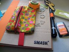 love the idea of a little zipper pouch attached to elastic to hold all of the smash book supplies.  must make this