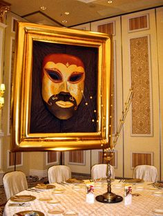 A giant Venetian masquerade mask inside a golden inflatable frame, and Venetian dinner ware and table centrepiece.  Perfect for a Venetian-themed event.