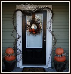 Doorway is embellished with grapevine, white lights, & stacked Faux pumpkins with embellished candle ring and placed on spanish moss. Love the simple symmetry design.
