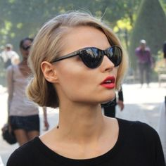 Epitome of beauty, matte coral lips, simple bun and cat eye sunglasses