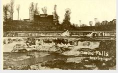 The Fall Creek Falls are now part of Falls Park in Pendleton. In this picture, factories line the banks and a railroad trestle is clearly seen.