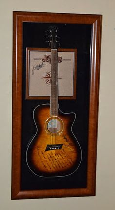 """Jimmy Buffett Custom Designed Acoustic Guitar Display is custom designed with compliment hard wood display case lined in black suede with solid hard wood opening door. Hand signed Changes In Latitudes Changes In Attitudes Album Cover with gorgeous Michael Kelly Electric/Acoustic Guitar and Jimmy wrote the lyrics to his most famous song: Changes In Latitudes Changes In Attitudes on the entire face of guitar! Measures: 45"""" x 20"""" x 8"""" #jimmybuffett #signedguitars #rockstargallery"""