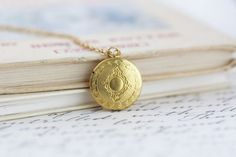 This delicate, ornate round locket opens up so you can pop a photo or momento inside. The back of the locket is smooth and the front is a lovely Victorian style with a floral edging.  Available on shorter or longer length chain.  The locket is made from brass and the chain is a delicate gold plated brass.