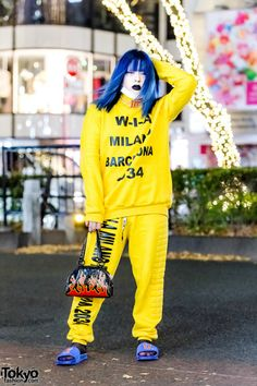 Shoushi on the street in Harajuku wearing a yellow WIA setup with a Diminish choker, Current Mood handbag, and Fenty slippers. Full Look