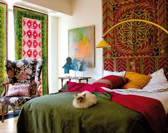 Bedroom, artist's home. Micasa Magazine. Love the tapestry as headboard with bold bed colors.