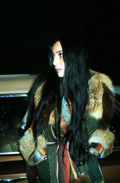 Cher, dear black hair, mexican blanket, fur, forest green. Live through anything