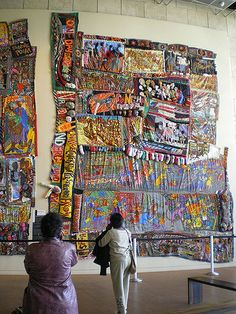 """One of the first things you see when you enter the Freedom Center is Aminah Robinson's amazing """"quilts"""" -- what she calls """"RagGonNons"""" because they """"rag on and on.""""  They both tell a story of her family's journeys beginning -- in the upper left corner -- in Africa.  The medium: cloth (including socks), thread, buttons, beads, ties, paper, paint, graphite, shells, and music boxes.  The work was a public art commission, and it's stunning."""