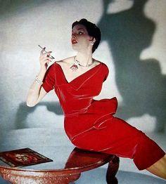 Model wearing a red velvet cocktail dress, 1950s.