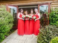 Bridesmaids in stunning red dresses pose for a shot outside the entrance to the Danube Suite at Hungarian Hall