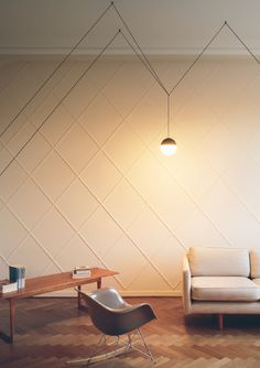 STRING LIGHTS by Michael Anastassiades for FLOS brightens this spacious, minimalist interior featuring hardwood floors, bare walls and contemporary seating. Shop String Lights & more FLOS iconic designs on our website.