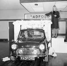 Actor Peter Sellers drives a Circassian blue Mini - a birthday present to his wife, Britt Ekland - through a gigantic cake after officially opening the new showroom for Harold Radford, Hammersmith, London. 1965.