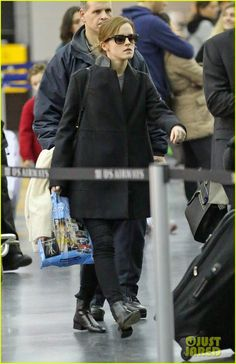 Emma Watson waits in line after arriving at JFK Airport on Sunday (January 19) in New York City
