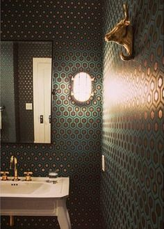 The bathroom's teal-and-gold hexagonal-patterned wallpaper adds a lively vibe to the transitional space, while a white pedestal sink adds a traditional touch. Towel hooks featuring gold bull sculptures hang on the wall, providing an eclectic, funky edge. Glamorous Bathroom, Modern Bathroom, Small Bathroom, Boho Bathroom, Chic Bathrooms, Bathroom Colors, Hexagon Wallpaper, Of Wallpaper, Bathroom Wallpaper Funky