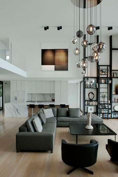 white + marble + grey sofa + cluster lighting + glass + wall shelving + art i heart