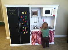 DIY play kitchen made from an old tv stand from goodwill.  Most of the stuff was found around the house from old supplies, silver bowl for sink with old sink attachments, cds painted black for burners, ikea stationary box for microwave, ikea racks for pots and curtain, painted with chalkboard and magnetic paint.