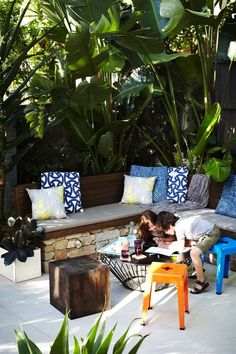 Private outdoor living rooms created with white bird of paradise, palm trees and shade loving tropical plants: