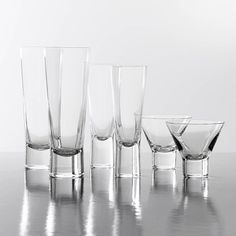 Aarne Crystal Glasses -- Beer, Champagne, Cocktail Glasses With their clean, subtle lines, these glasses are a classic of tabletop design. The tapered lead-free crystal glasses feature a signature weighted base for stability. Designed by Göran Hongell in 1948, represented in the Museum's collection, displayed in several exhibitions. Made by Iittala. Sets of two.