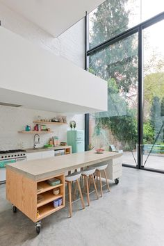 Mix-and match keuken met betonnen verrijdbare werktafel om de flexibiliteit van de ruimte te vergroten.