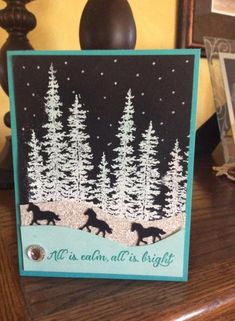 """By n.d.stamper at Splitcoaststampers. Stamp trees from """"Wonderland"""" (Stampin' Up) on black cardstock. Add snow with white chalk marker. Cut hills from glimmer paper and Bermuda Bay cardstock. Stamp sentiment; add bling and cardstock base."""