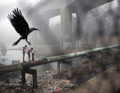 Aseo matutino en una tubería de agua sobre un desagüe de aguas residuales, en Nueva Delhi. Fotografía de Kevin Frayer