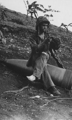 Using an unexploded 16-inch naval shell for a resting place Marine Private First Class Raymond Hubert shakes the pebbles from his shoe Saipan 1944.