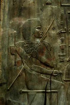 """Wooden panel portrait, tomb of Hesire (""""Chief Architect"""" and """"Chief Dentist"""") at Saqqara in reign of Djoser (Netjerikhet, 2667-2648 bc, 3rd Dynasty). Hesire left hand holds a long staff and the scribal outfit of a palette with discs of red and black pigments, a long pen holder and a small leather bag for more supplies, and his right hand holds the sceptre of authority and power. Egpytian Museum, Cairo."""