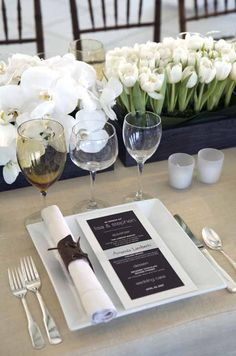 Tables are set with orchids and tulips in wooden troughs. Each place setting features a brown menu and a napkin wrapped in suede.
