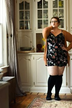 Vintage, sophisticated, sexy style. Plus-size, curvy outfit with floral romper, knee-high socks, and camel colored cardigan.  The Classy Junk