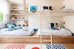 Schlafplatz für drei Kinder dank Podest und Hochbett im geteilten Kinderzimmer.