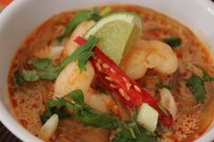 Laksa is a Malaysian soup made from laksa flavour spicy curry, coconut cream, noodles, prawns/shrimp, chicken and lots of fresh toppings. This recipe is considered to be a cheat version because it uses laksa paste, however the results are still very yummy. You can vary the ingredients in the soup to your own taste.  I had trouble finding fish balls and fried tofu puffs in my region so I replace the balls with extra green prawns/shrimp and fried my own tofu (I cut them into 1 cm by 1 cm…