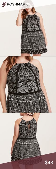"""Torrid Insider Paisley Print Gauze Trapeze Dress """"This is a #nofilterneeded festival style. Black gauze has free spirit feels with a lightweight trapeze construction. The swirling white paisley print matches your grooving, along with an adjustable halter tie neck. The keyhole cutout is boho chic with embellished tassels. Crochet insets detail the drop-down waist and back."""" New with tags, size 2X. torrid Dresses Midi"""