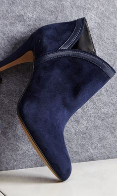 Suede bootie with faux leather piping, a pointed toe and an easy side zipper.