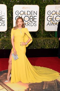 Jennifer Lopez is every part the star in a caped yellow gown with high slit by Giambattista Valli Couture and striking Jimmy Choo pumps.   - HarpersBAZAAR.com