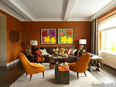 "Orange Living Room: In the living room, midcentury modern pieces mix with contemporary pieces. ""I'm not afraid of color,"" designer Heather Moore says. ""I knew I wanted to use orangey autumnal tones, and I chose Ralph Lauren's Cork for the walls. It's a burnt umber, a saturated color that doesn't read as flat. It has more reflectivity and depth than that."