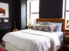 Bedroom with dar blue walls and a mustard yellow headboard in the Brooklyn home of Joanna Goddard