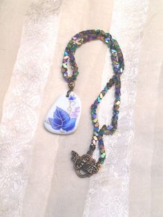 """Handmade Porcelain Leaf Necklace W/ Unique by #NorthCoastCottage, $49.00. The focal bead on this 22.5"""" necklace is a smoothed shard of hand-painted porcelain. The multicolor glass beads are full of interest, light, perspective and geometry. The clasp is a bronze #dragonfly toggle that sweetly echoes the beauty of nature depicted in the leaf motif on the pendant. No one will have a #necklace like it, but most everyone will notice and ask you about it. #jewelry #etsy"""