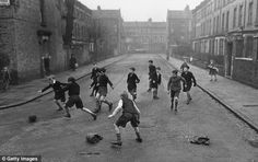 Boys playing football in a residential street in 1950's London. Children today do not have the freedom these children had.