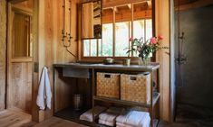 There are three baths; this one has an industrial-style sink unit and square woven baskets hold bath essentials.